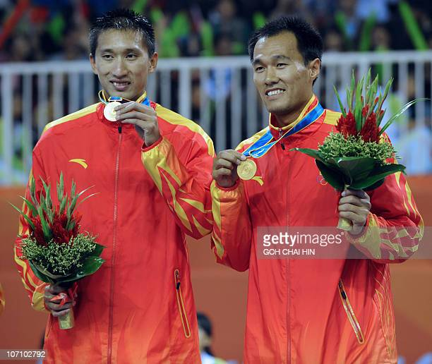 Xu Linyin and Wu Penggen of China pose with their gold medals during the award ceremony in the beach volleyball men's competition at the 16th Asian...