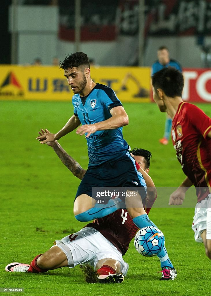 Xu Xin (back) of China's Guangzhou Evergrande fights for the ball with Christopher Naumoff (front) of Sydney FC during their AFC Champions League group stage football match in Guangzhou, in China's Guangdong province on May 3, 2016. / AFP / STR