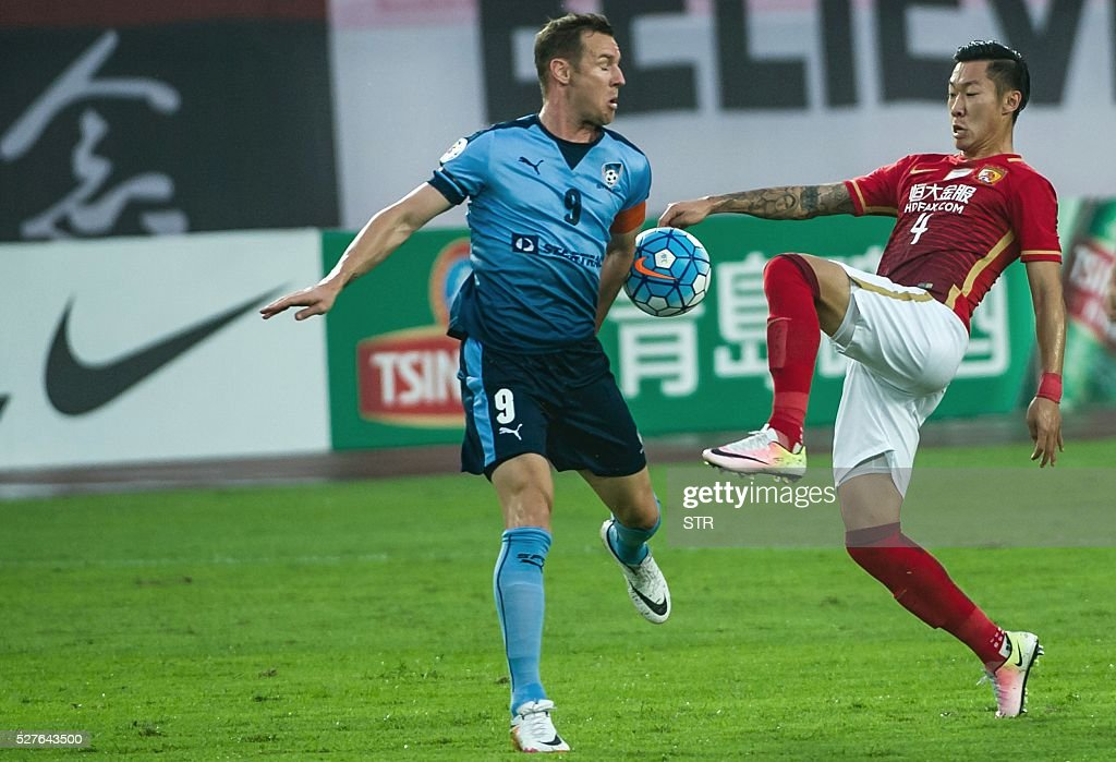 Xu Xin (R) of China's Guangzhou Evergrande fights for the ball with Shane Smeltz of Sydney FC during their AFC Champions League group stage football match in Guangzhou, in China's Guangdong province on May 3, 2016. / AFP / STR