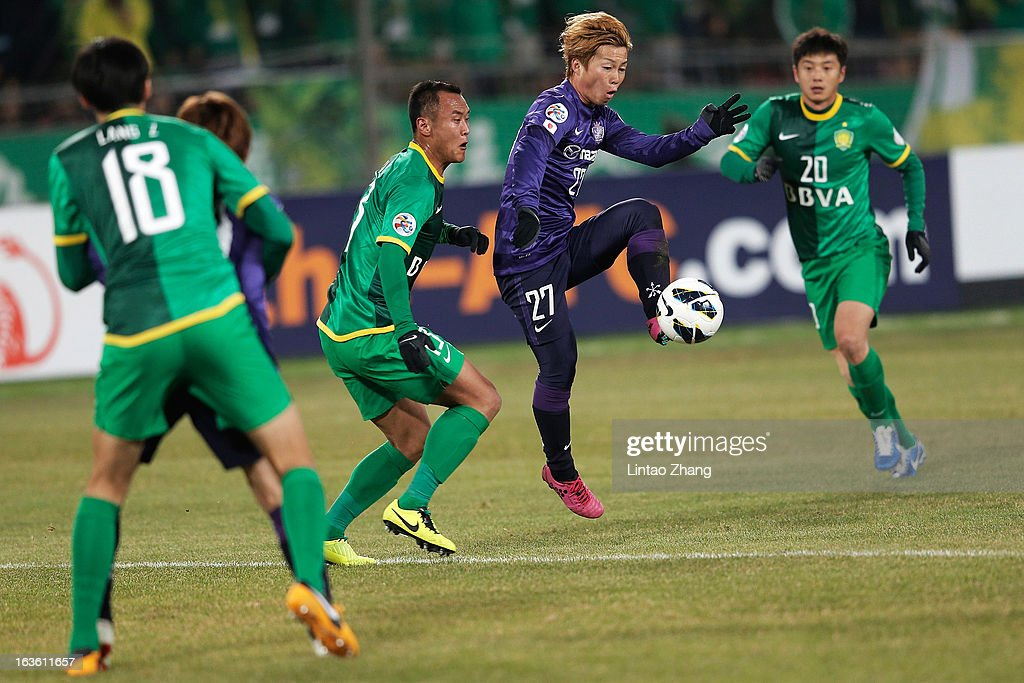 Xu Yunlong (2nd-L) of Beijing Guo'an challenges Kohei Shimizu (2nd-R) of Hiroshima Sanfrecce during the AFC Champions League Group match between Hiroshima Sanfrecce and Beijing Guoan at Beijing Workers' Stadium on March 13, 2013 in Beijing, China.