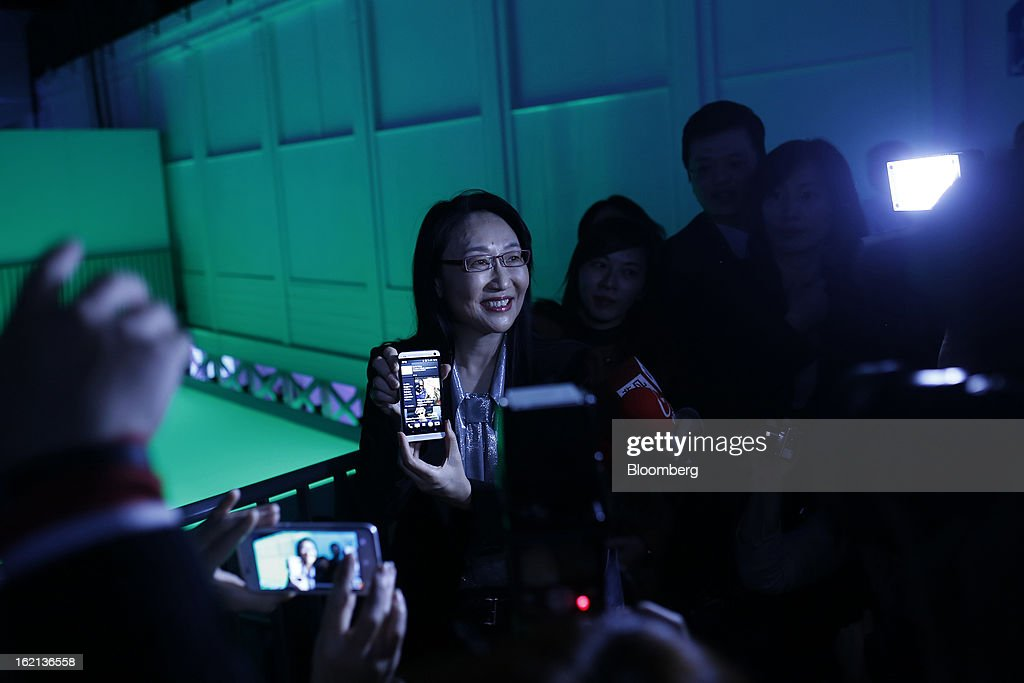 Xue Hong, chairman of the board of HTC Corp., center, holds a new HTC One smartphone for the media during a launch in London, U.K., on Tuesday, Feb. 19, 2013. HTC Corp. introduced its new flagship HTC One smartphone at a launch event in London today. Photographer: Simon Dawson/Bloomberg via Getty Images
