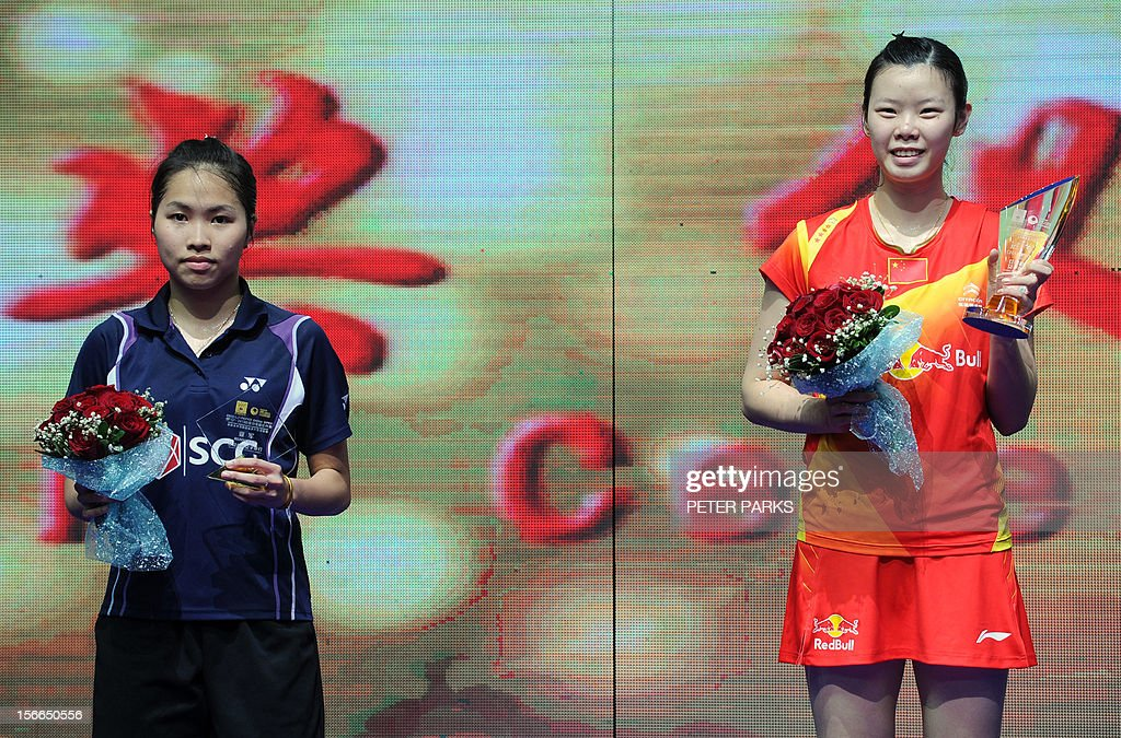 Xuerui Li of China (R) celebrates on the podium after beating Ratchanok Intanon of Thailand (L) in the women's singles final at the China Open badminton tournament in Shanghai on November 18, 2012. AFP PHOTO/Peter PARKS