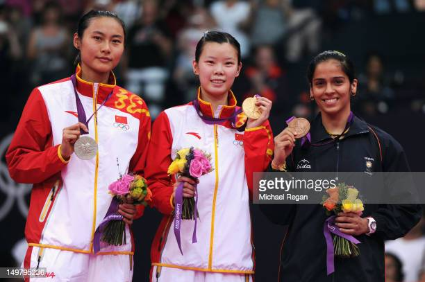 Xuerui Li of China celebrates on the podium with her Gold medal Yihan Wang of China the Silver and Saina Nehwal of India the Bronze following the...