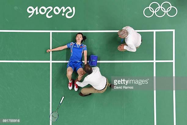 Xuerui Li of China lays injured on the court during the Women's Badminton Singles Semifinal Match between Carolina Marin of Spain and Xuerui Li of...