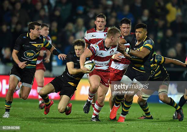 xxxx of Northampton Saints tackles Joe Mullis of Gloucester Rugby is tackled by Sam Olver and Lewis Ludlam of Northampton Saints tackles during the...