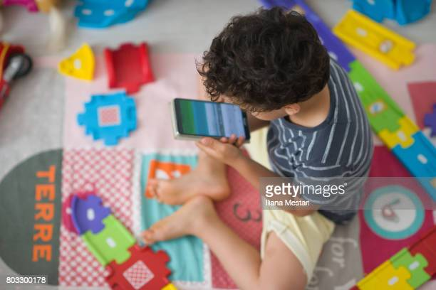 4 y old boy holding a smart phone