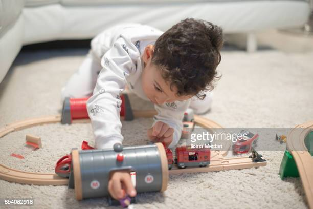 4 y old playing with a wooden train on the floor