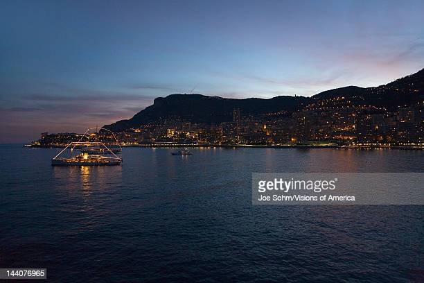 Yacht and seaside night view of MonteCarlo with lights at dusk in the Principality of Monaco Western Europe on the Mediterranean Sea