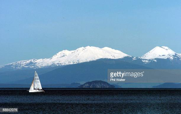 A yacht soaks up the sun as it crosses Lake Taupo with Mt Ruapehu and the Tongariro Ranges in the background on a beautiful spring day in Taupo New...