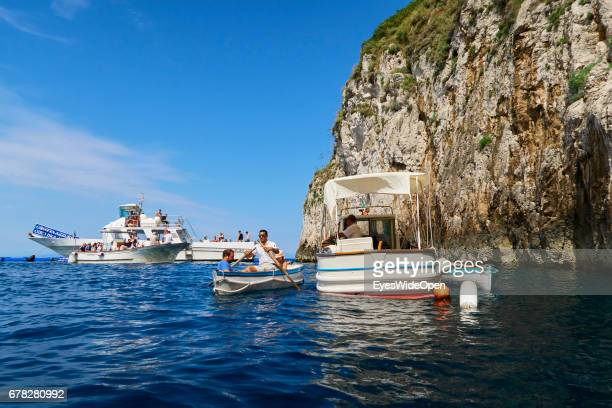Yachts and small rowing boats with Tourists in front of the Blue Grotto at the Island of Capri on June 24 2015 in Naples Italy