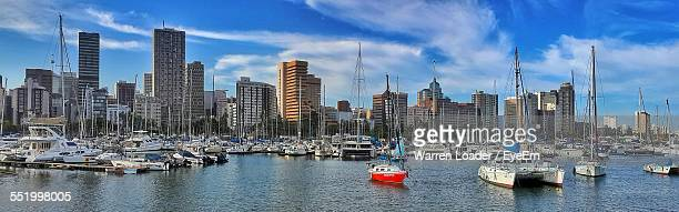 Yachts At Commercial Dock With City In Background
