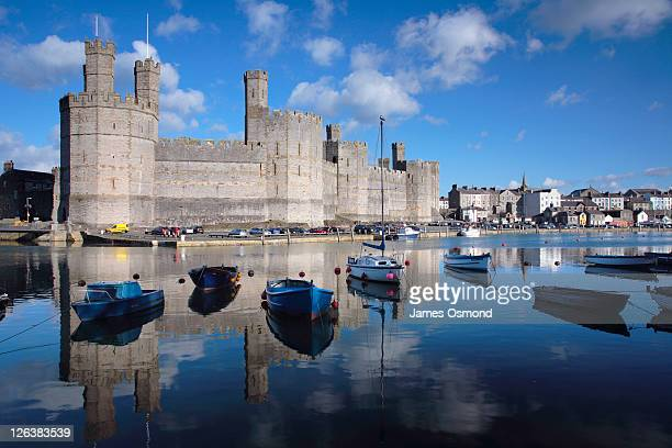 Yachts moored alongside Caernarfon Castle constructed by King Edward I in 1283 at the mouth of the River Soilont in Gwynedd