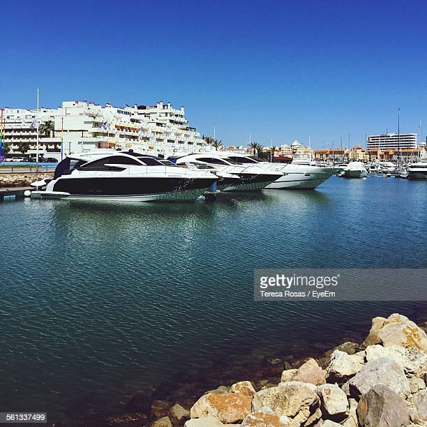 Yachts Moored At Harbor Against Clear Blue Sky