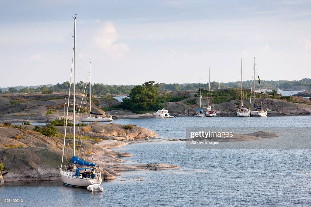 Yachts moored at rocky coast