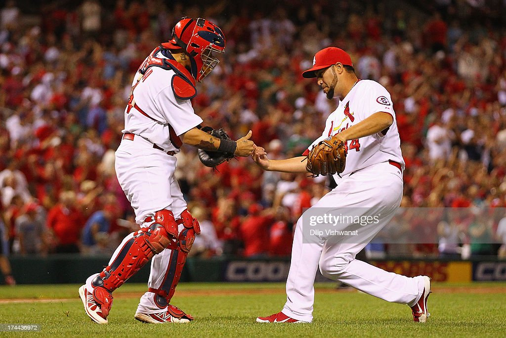<a gi-track='captionPersonalityLinkClicked' href=/galleries/search?phrase=Yadier+Molina&family=editorial&specificpeople=172002 ng-click='$event.stopPropagation()'>Yadier Molina</a> #4 and reliever <a gi-track='captionPersonalityLinkClicked' href=/galleries/search?phrase=Edward+Mujica&family=editorial&specificpeople=836179 ng-click='$event.stopPropagation()'>Edward Mujica</a> #44 both of the St. Louis Cardinals congratulate each other after beating the Philadelphia Phillies at Busch Stadium on July 25, 2013 in St. Louis, Missouri. The Cardinals beat the Phillies 3-1.