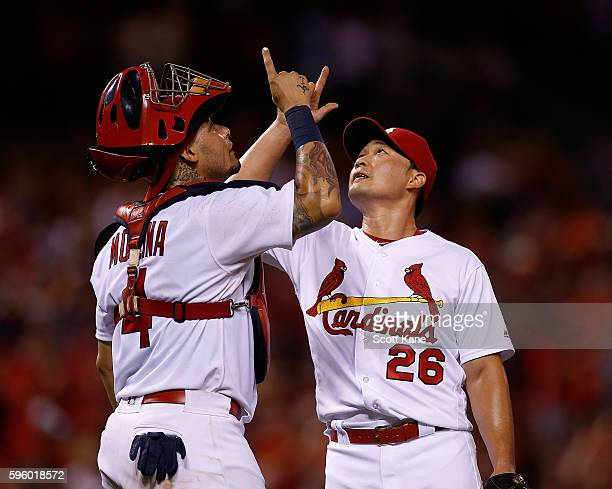 Yadier Molina and Seung Hwan Oh of the St Louis Cardinals point skyward in celebration after the Cardinals defeated the Oakland Athletics 31 during a...