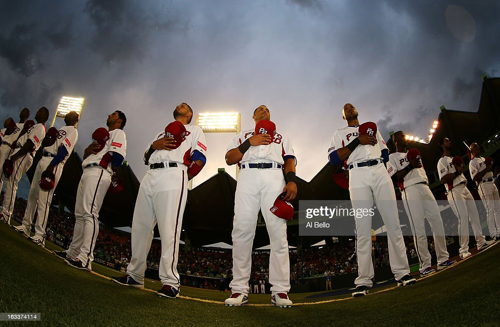Yadier Molina #4, Carlos Beltran #15, and Alex Rios #51 of Puerto Rico stand for the national anthem before their game against Spain during the first round of the World Baseball Classic at Hiram Bithorn Stadium on March 8, 2013 in San Juan, Puerto Rico.