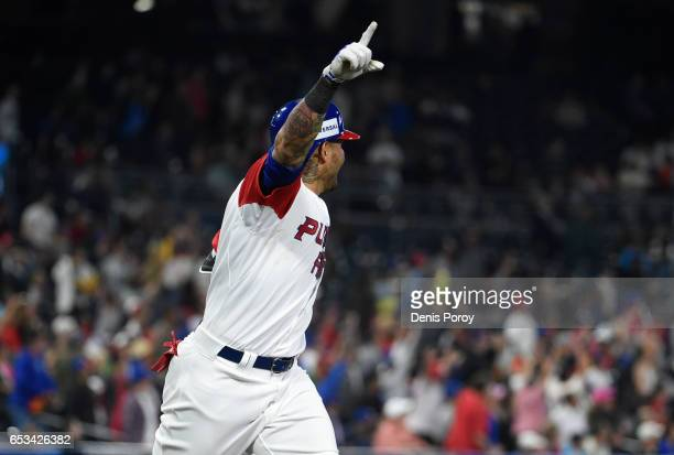 Yadier Molina of Puerto Rico celebrates after hitting a solo home run during the sixth inning of the World Baseball Classic Pool F Game One between...