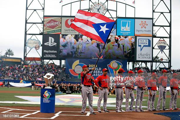 Yadier Molina of Puerto Rico waves his countries flag prior to playing against the Dominican Republic during the Championship Round of the 2013 World...
