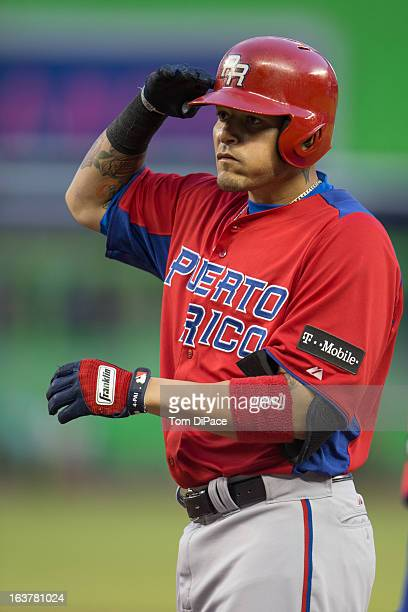 Yadier Molina of Team Puerto Rico salutes his teammates from first base after hitting a single in the top of the first inning of Pool 2 Game 4...
