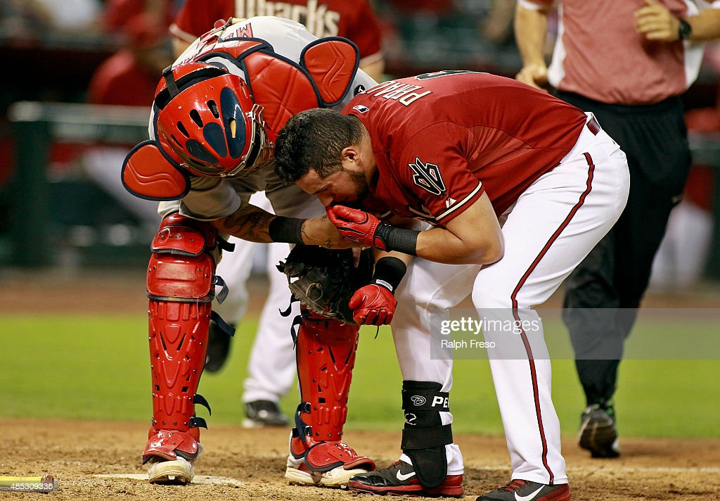 Yadier Molina #4 of the St Louis Cardinals (L) assists David Peralta #6 of the Arizona Diamondbacks after Peralta was hit in the head by his own foul ball during the ninth inning of a MLB game at Chase Field on August 26, 2015 in Phoenix, Arizona. The Cardinals defeated the Diamondbacks 3-1.