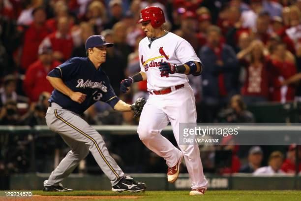 Yadier Molina of the St Louis Cardinals avoids an attempted tag attempt by Zack Greinke of the Milwaukee Brewers as Molina scores by Jaime Garcia...