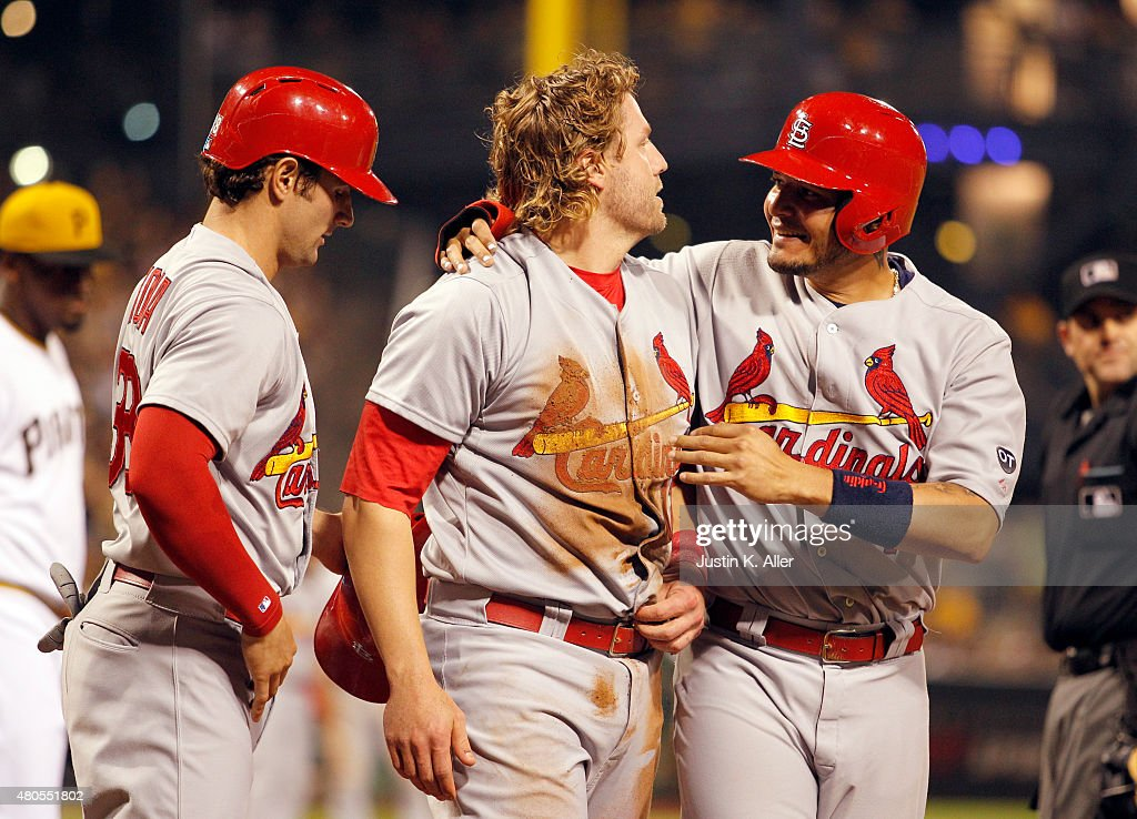 Yadier Molina #4 of the St. Louis Cardinals celebrates with Mark Reynolds #12 and Pete Kozma #38 after scoring in the tenth inning on a two RBI double during the game at PNC Park on July 12, 2015 in Pittsburgh, Pennsylvania.
