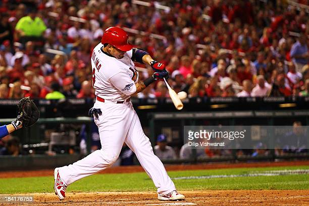 Yadier Molina of the St Louis Cardinals hits a single in the fourth inning against the Los Angeles Dodgers during Game One of the National League...