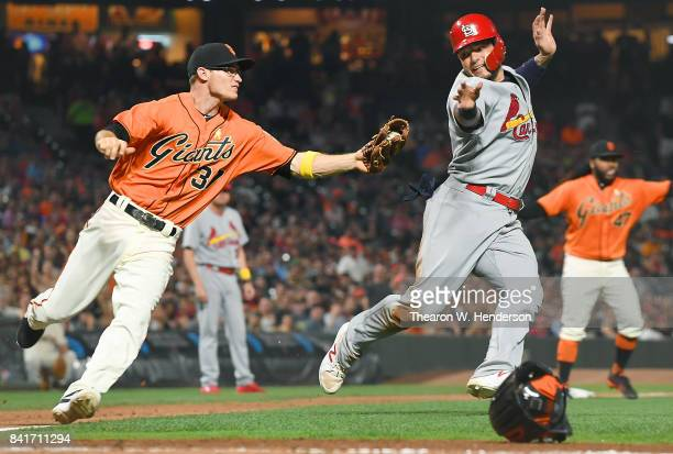 Yadier Molina of the St Louis Cardinals is called out for running out of the base line while chased in a runbown by Kelby Tomlinson of the San...