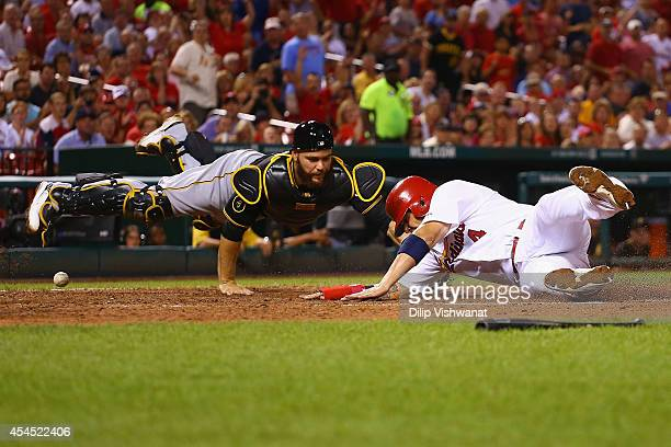 Yadier Molina of the St Louis Cardinals scores a run against Russell Martin of the Pittsburgh Pirates in the fourth inning at Busch Stadium on...