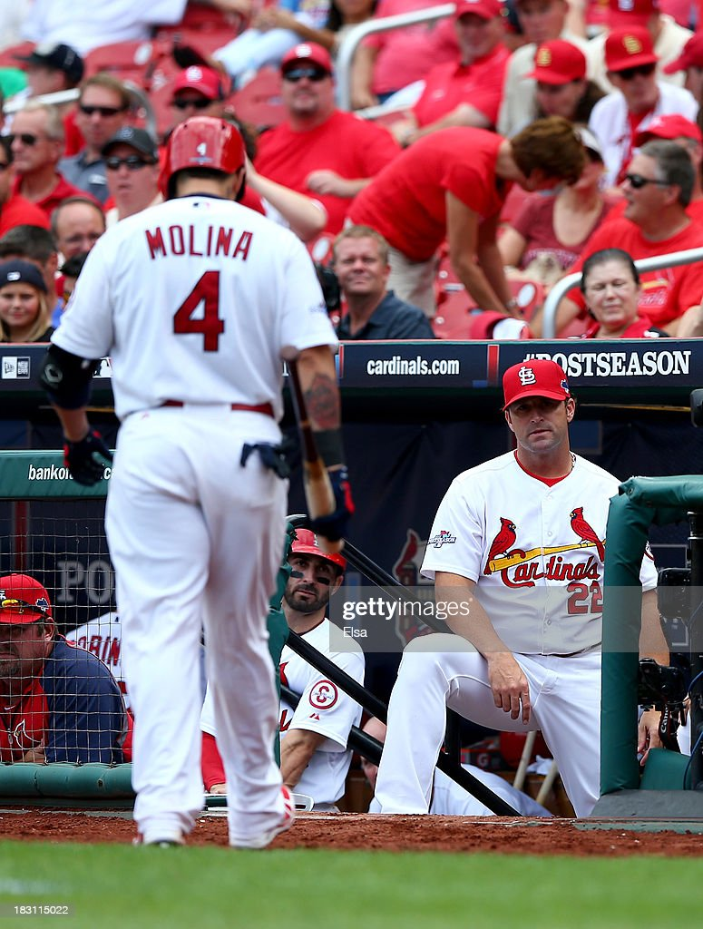Yadier Molina #4 of the St. Louis Cardinals walks back to the dugout towards manager Mike Matheny #22 after striking out in the ninth inning against the Pittsburgh Pirates during Game Two of the National League Division Series at Busch Stadium on October 4, 2013 in St Louis, Missouri.