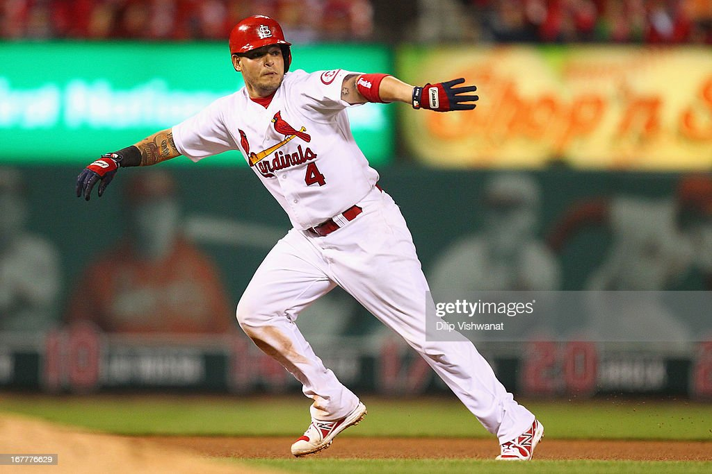 Yadier Molina #4 of the St. Louis Cardinals waves David Freese #23 also of the St. Louis Cardinals to second base after Molina was caught in a run down against the Cincinnati Reds in the eighth inning at Busch Stadium on April 29, 2013 in St. Louis, Missouri. The Reds beat the Cardinals 2-1.