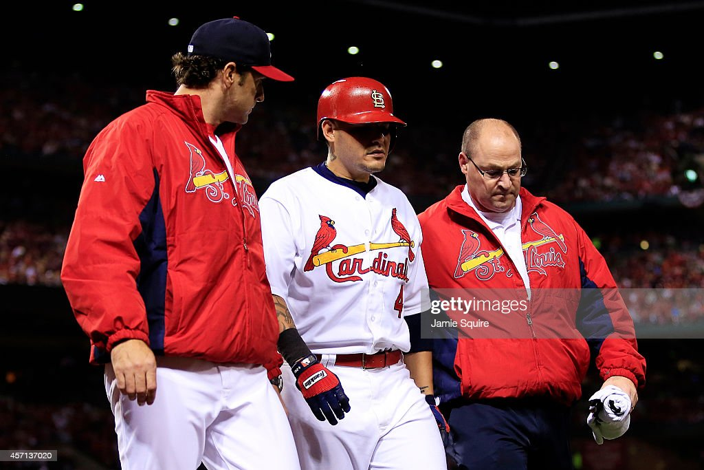 <a gi-track='captionPersonalityLinkClicked' href=/galleries/search?phrase=Yadier+Molina&family=editorial&specificpeople=172002 ng-click='$event.stopPropagation()'>Yadier Molina</a> #4 receives attention from manager <a gi-track='captionPersonalityLinkClicked' href=/galleries/search?phrase=Mike+Matheny&family=editorial&specificpeople=171706 ng-click='$event.stopPropagation()'>Mike Matheny</a> #22 and trainer Greg Hauck in the sixth inning during Game Two of the National League Championship Series against the San Francisco Giants at Busch Stadium on October 12, 2014 in St Louis, Missouri.