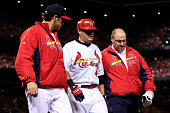 Yadier Molina receives attention from manager Mike Matheny and trainer Greg Hauck in the sixth inning during Game Two of the National League...