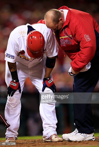 Yadier Molina receives attention from trainer Greg Hauck in the sixth inning during Game Two of the National League Championship Series against the...