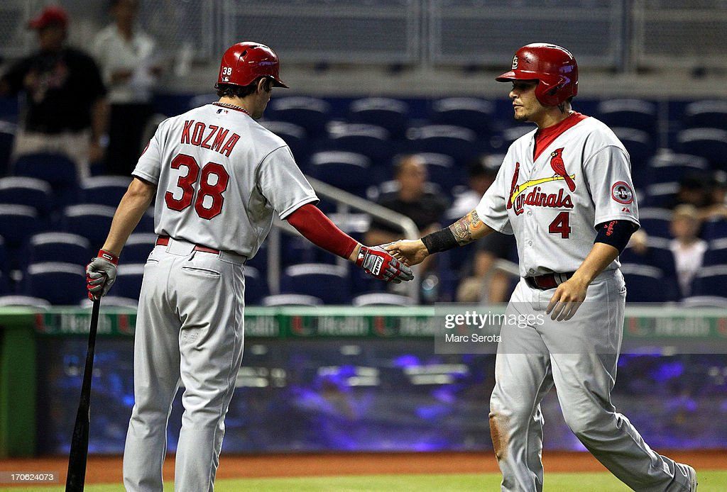 Yadler Molina #4 of the St. Louis Cardinals celebrates scoring a run with teamate <a gi-track='captionPersonalityLinkClicked' href=/galleries/search?phrase=Pete+Kozma&family=editorial&specificpeople=6800748 ng-click='$event.stopPropagation()'>Pete Kozma</a> #38 during the first inning at Marlins Park on June 15, 2013 in Miami, Florida.