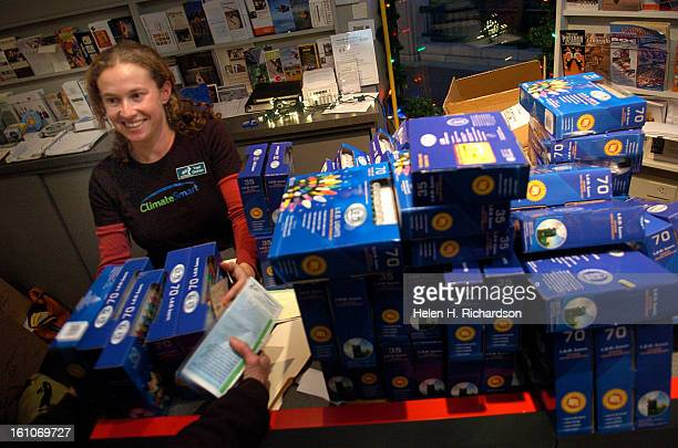 Yael Gichon <cq> an employee with the City of Boulder Envirnomental Affairs department hands out boxes of LED lights to awaiting folks who had just...