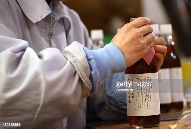 A Yagisawa Shouten Co employee performs a final inspection on a bottle of dashi a Japanese soup stock made from fish and kelp at the company's...