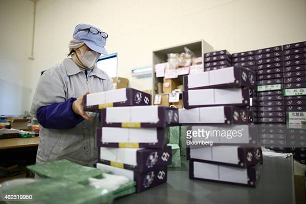 A Yagisawa Shouten Co employee places packaged bottles of soy sauce into paper bags at the company's factory in Ichinoseki Iwate prefecture Japan on...
