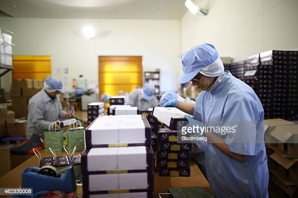 Yagisawa Shouten Co employees place packaged bottles of soy sauce into paper bags at the company's factory in Ichinoseki Iwate prefecture Japan on...