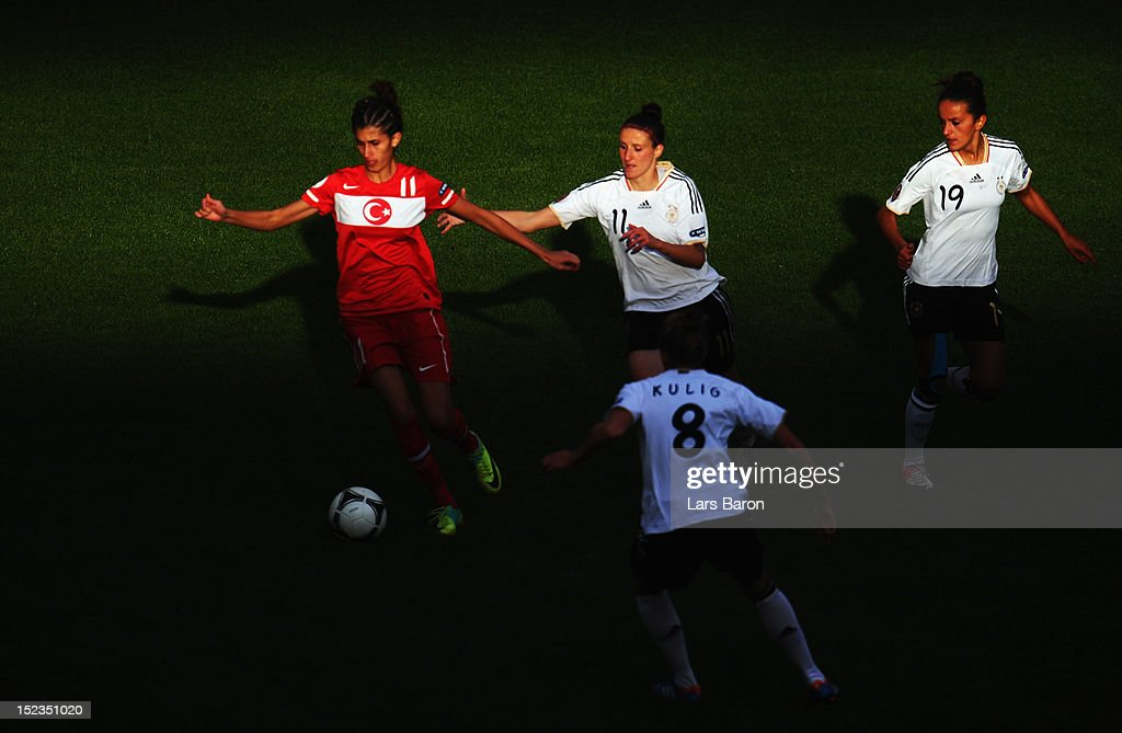 Yagmur Uraz of Turkey is challenges by <a gi-track='captionPersonalityLinkClicked' href=/galleries/search?phrase=Anja+Mittag&family=editorial&specificpeople=210615 ng-click='$event.stopPropagation()'>Anja Mittag</a>, Fatmire Bajramaj and <a gi-track='captionPersonalityLinkClicked' href=/galleries/search?phrase=Kim+Kulig&family=editorial&specificpeople=2194725 ng-click='$event.stopPropagation()'>Kim Kulig</a> of Germany during the UEFA Womens Euro 2013 qualification match between Germany and Turkey at Schauinsland-Reisen-Arena on September 19, 2012 in Duisburg, Germany.