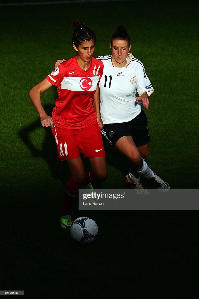 Yagmur Uraz of Turkey is challenges by <a gi-track='captionPersonalityLinkClicked' href=/galleries/search?phrase=Anja+Mittag&family=editorial&specificpeople=210615 ng-click='$event.stopPropagation()'>Anja Mittag</a> of Germany during the UEFA Womens Euro 2013 qualification match between Germany and Turkey at Schauinsland-Reisen-Arena on September 19, 2012 in Duisburg, Germany.