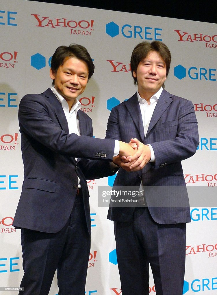 Yahoo Japan CEO Manabu Miyasaka (L) and Yoshikazu Tanaka, founder and CEO of mobile gaming giant GREE, shake hands after reaching agreement to co-develop social games at a press conference on November 8, 2012 in Tokyo, Japan.