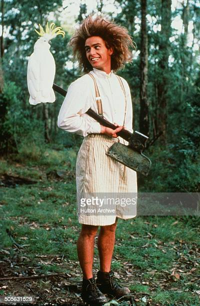 Yahoo Serious poses with his bird in a scene from the Warner Bros movie 'Young Einstein' circa 1988