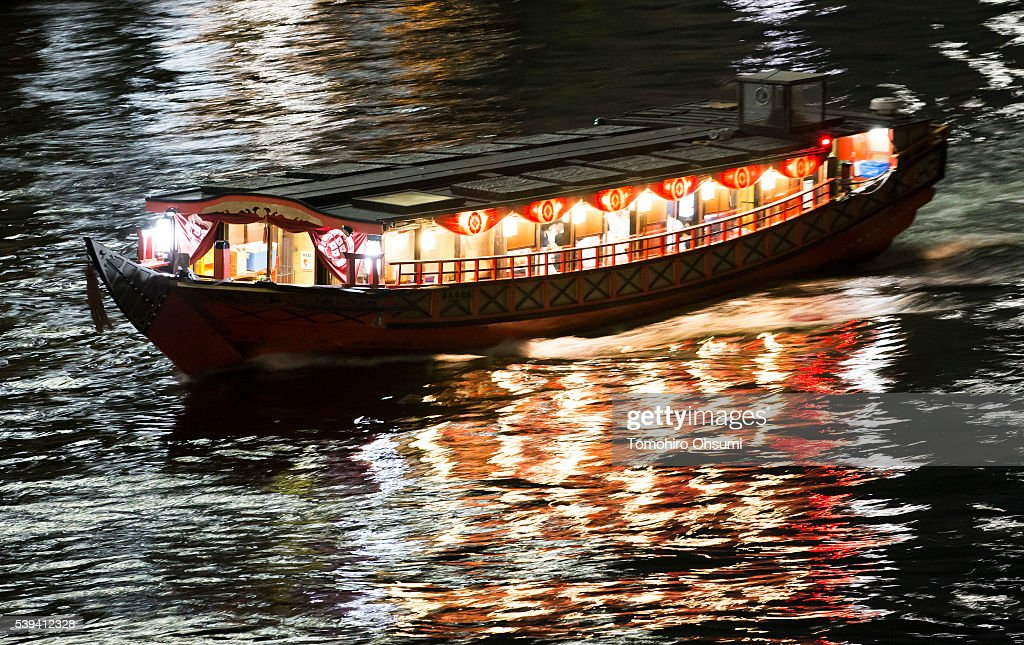 A yakatabune, or traditional low barge style boat, sails on the Sumida River at night on June 10, 2016 in Tokyo, Japan. About 35 companies operate over 100 yakatabune boats in Tokyo offering services such as dinner or karaoke inside the boats while cruising in Tokyo's bay area, according to the Tokyo Yakatabune Association.