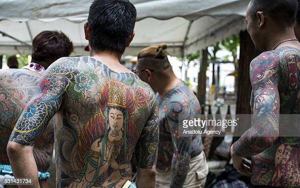 Yakuza members proudly display their tattoos during the second day of the Sanja Matsuri Festival in Tokyo's Asakusa district on May 14 2016 This...
