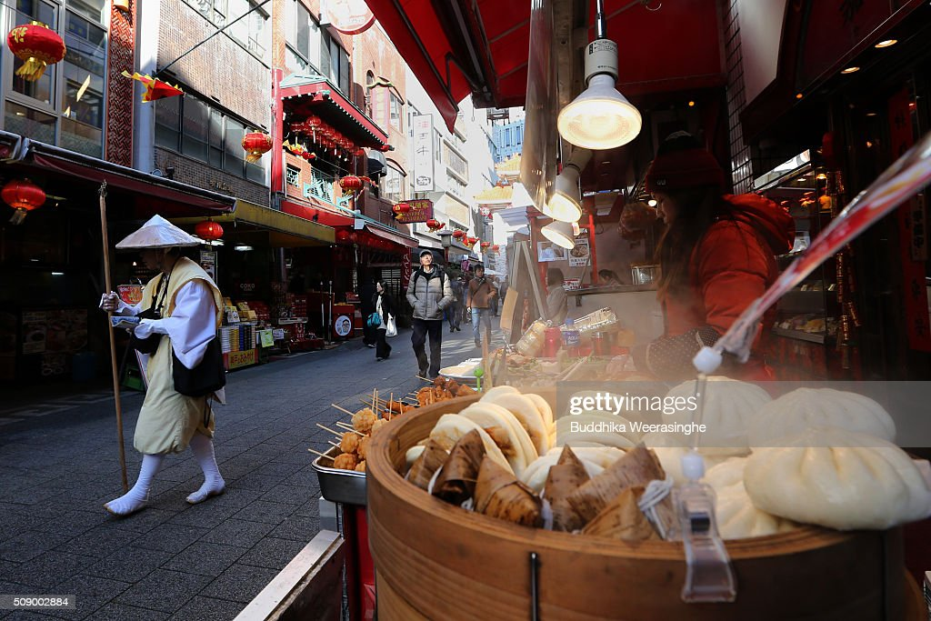 Yamabushi, Japanese Buddhist monk walks pass the Chinese meat buns stall at the Nankinmachi China Town on February 8, 2016 in Kobe, Japan. In Nankinmachi, the district known as Kobe Chinatown, tourists enjoyed Chinese food, lion dance and the parade organized to celebrate the Lunar New Year.