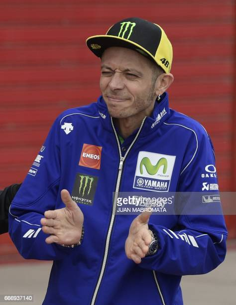 Yamaha biker Valentino Rossi of Italy gestures at pit lane to congrats KTM biker Andrea Migno of Italy who finished in the 5th place on the Moto3...