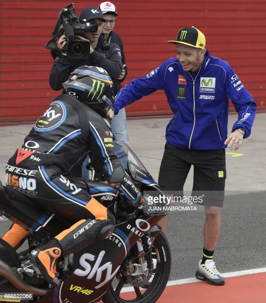 Yamaha biker Valentino Rossi of Italy greats Andrea Migno on his KTM after finishing the Moto3 race of Argentina Grand Prix at Termas de Rio Hondo...