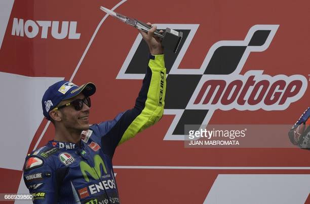 Yamaha biker Valentino Rossi of Italy raises his 2nd place trophy to his supporters at the podium of the MotoGP race of Argentina Grand Prix at...